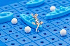 Anhänger in Form eines Goldsalamanders nimmt Kriegsschiffe eines Spielzeugs in Angriff Stockbild