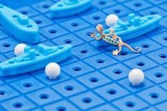 Anhänger in Form eines Goldsalamanders nimmt Kriegsschiffe eines Spielzeugs in Angriff Stockbilder