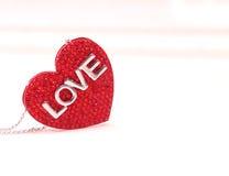 Anhänger in Form von roten Herzen auf einem weißen Hintergrund Stockbilder