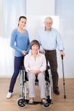 Anhörigvårdare med rörelsehindrade höga par Arkivbilder