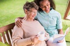 Anhörigvårdare och pensionär i trädgård royaltyfria bilder