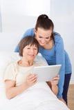 Anhörigvårdare- och pensionärkvinna som använder den digitala minnestavlan Arkivbild