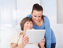 Anhörigvårdare- och pensionärkvinna som använder den digitala minnestavlan Arkivfoto