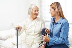 Anhörigvårdare som gör blodtryckövervakning för hög kvinna Arkivfoto