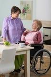 Anhörigvårdare som hjälper den rörelsehindrade kvinnan Arkivbilder