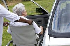 Anhörigvårdare som hjälper en hög dam för handikappade personer att få inom av hennes bil Fotografering för Bildbyråer