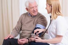 Anhörigvårdare som kontrollerar höga blodtrycket Royaltyfria Bilder