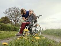 Anhörigvårdarekomfort oroade den höga kvinnan med rullstolen arkivbild