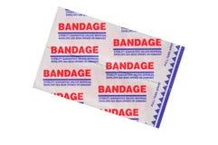 Anhaftende Erste-Hilfeverbände beim Verpacken auf Weiß Lizenzfreies Stockfoto