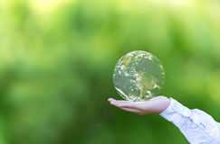 Anhalten einer glühenden Erdekugel in seinen Händen stockbild