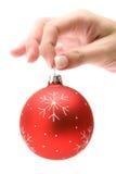 Anhalten einer roten Weihnachtsbaum-Kugel Stockfotografie