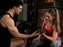 Anhebende Dummköpfe der Frau mit ihrem persönlichen Trainer Stockfotos