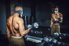Anhebende Dummköpfe des athletischen Mannes des Afroamerikaners und Arbeiten an seinem Bizeps vor dem Spiegel an der Turnhalle sc Lizenzfreie Stockfotos