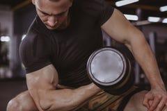 Anhebende Dummköpfe des männlichen Bodybuilders an der Turnhalle stockfoto