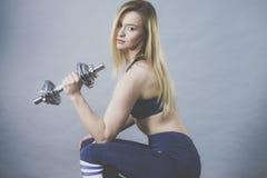 Anhebende Dummkopfgewichte der geeigneten Frau Stockfoto