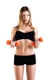 Anhebende Gewichte der attraktiven Frau und Lächeln an der Kamera stockfotos