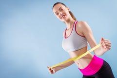 Anhebende Gewichte der attraktiven Frau und Lächeln an der Kamera Stockfoto