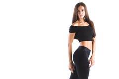 Anhebende Gewichte der attraktiven Frau und Lächeln an der Kamera Sportfrau in der schwarzen Sportkleidung Lizenzfreies Stockfoto
