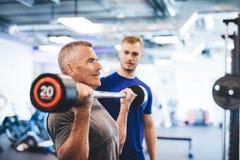 Anhebende Gewichte des älteren Mannes, überwacht vom Turnhallenassistenten lizenzfreies stockfoto