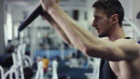 Anhebende Gewichte des jungen Mannes in einer Turnhalle, Seitenprofilabschluß herauf Schuss stock video