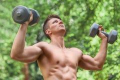Anhebende Gewichte des Mannes draußen im Park stockbild