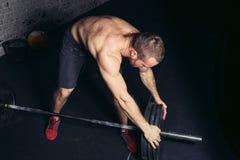 Anhebende Gewichte des Mannes Muskulöses Manntraining in der Turnhalle, die Übungen mit Barbell tut lizenzfreies stockfoto