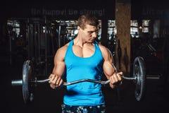 Anhebende Gewichte des muskulösen Mannes auf Bizepsen und Blicke auf das Bizeps Lizenzfreie Stockbilder
