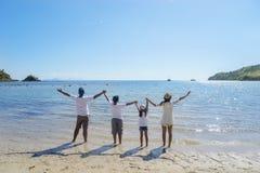 Anhebende Hände der jungen Familie zusammen auf dem Strand Stockbild