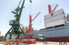 Anhebender Behälter des Hafenkranes und ladendes Schiff mit Fracht Stockfotos