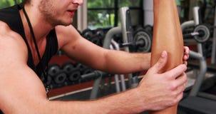 Anhebender Dummkopf der muskulösen Frau mit ihrem Trainer stock footage