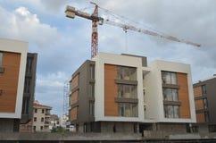 Anhebender Kran über einem Gebäude mit Arbeitskräften Stockfotos