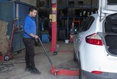 Anhebendes Auto des Mechanikers mit einem Hydraulik-Wagenheber in einer Werkstatt lizenzfreie stockfotografie
