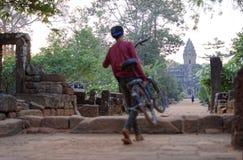 Anhebendes Fahrrad des Jungen über Wand Stockfoto