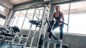 Anhebendes Gewicht der Frau auf untersetzter Maschine stockbilder
