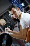 Anhebendes Gewicht des Mannes in einer Gymnastik Lizenzfreie Stockfotos