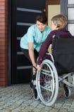 Anhörigvårdare som hjälper den rörelsehindrade kvinnan som hem skriver in Royaltyfri Fotografi