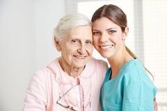 Anhörigvårdare som omfamnar den lyckliga pensionären Arkivfoto