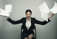 Anhry lady elegantly dressed throw a stack of papers to the came Stock Photography