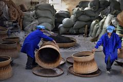 ANHUI PROVINCE, CHINA – CIRCA OCTOBER 2017: Men working inside a tea factory. Men working inside a tea factory with the big wicker basket, where si the stock image