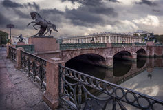 Anichkov bridge in a grey morning. Anichkov Bridge with sculptures of horses in a gray cloudy morning Stock Photography