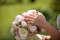 Anillo de bodas de las novias con el ramo Imagenes de archivo