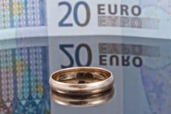 Anillo de bodas del oro en el fondo de billetes de banco euro Fotos de archivo libres de regalías
