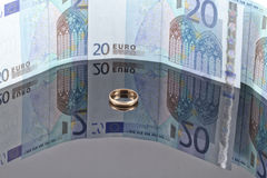 Anillo de bodas del oro en el fondo de billetes de banco euro Foto de archivo