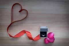 Anillo de bodas y cinta roja del corazón con los pétalos color de rosa rosados en superficie de madera con el espacio vacío para  Imagen de archivo