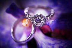 Anillo de compromiso del diamante en fondo púrpura Fotos de archivo libres de regalías
