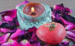 Anillo de compromiso en el jabón, pétalos color de rosa, velas con las llamas Foto de archivo