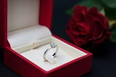 Anillo de compromiso moderno del diamante en rectángulo rojo Imagen de archivo
