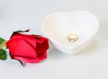 Anillo de diamante con el corazón rojo en un cuenco blanco de la forma del corazón Imagenes de archivo