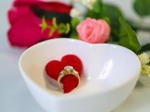 Anillo de diamante con el corazón rojo en un cuenco blanco de la forma del corazón Fotos de archivo libres de regalías