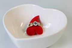 Anillo de diamante con el corazón rojo en un cuenco blanco de la forma del corazón, concepto Fotografía de archivo libre de regalías